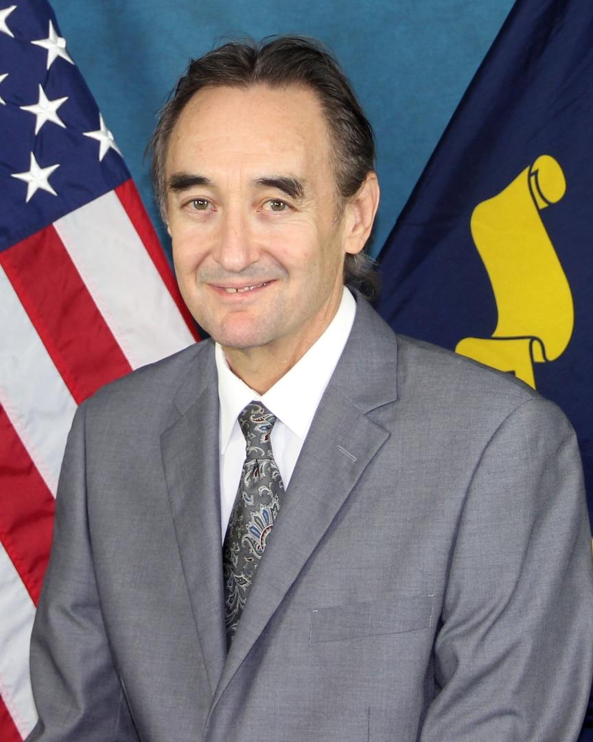 Portrait of Brett Hamilton (SSTM), NSWC Crane in front of an American flag.
