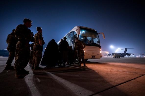 Airman assist Afghanistan evacuees onto a shuttle, Aug. 23, 2021, at Al Udeid Air Base, Qatar.