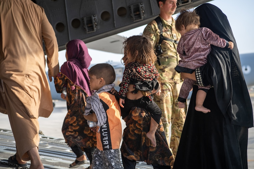 A woman and several children walk up the ramp of a military aircraft.