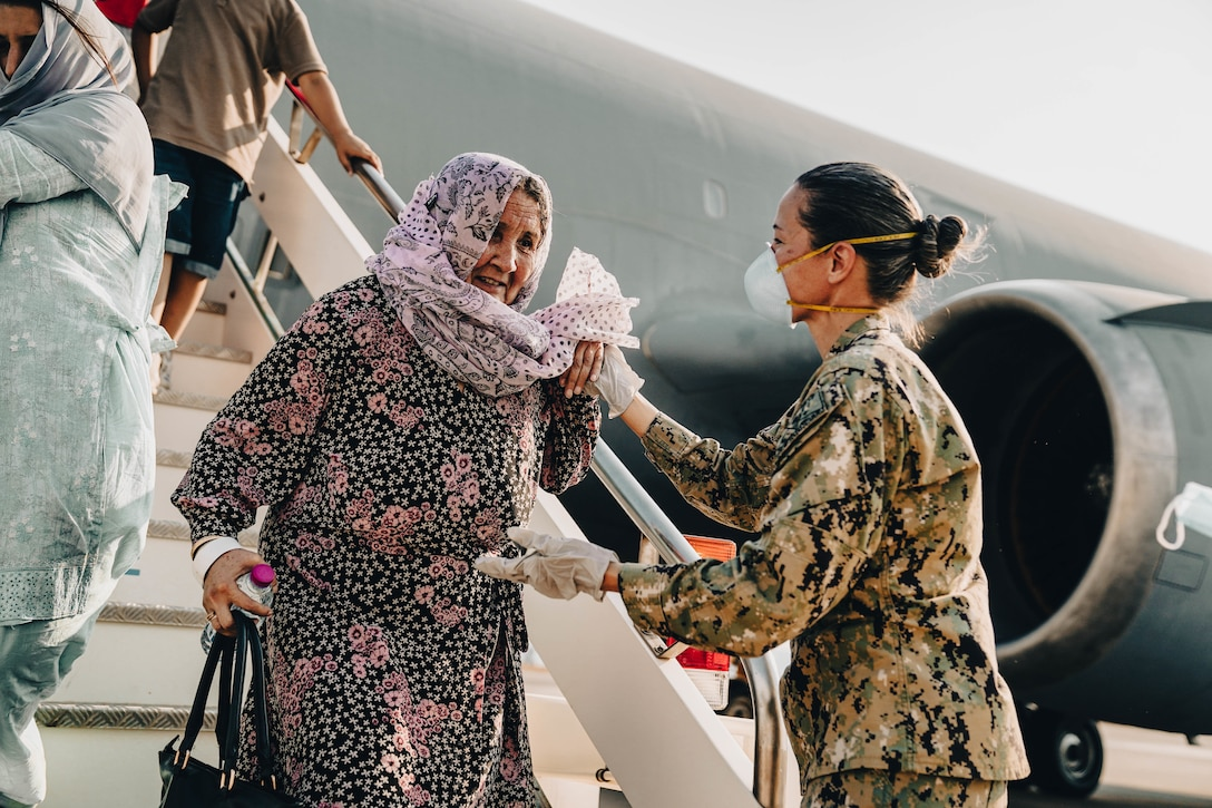 A woman in a military uniform assists an older woman down the stairs of a military aircraft.