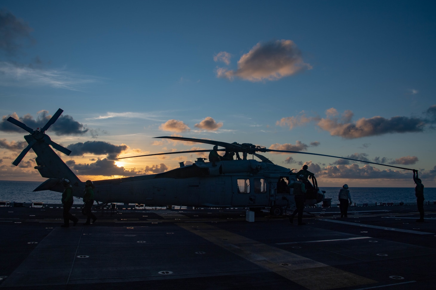 Sailors assigned to the forward-deployed amphibious assault ship USS America (LHA 6) conduct routine maintenance on an MH-60S Seahawk helicopter from the Helicopter Sea Combat Squadron (HSC) 25. America, flagship of the America Expeditionary Strike Group, along with the 31st Marine Expeditionary Unit, is operating in the U.S. 7th Fleet area of responsibility to enhance interoperability with allies and partners and serve as a ready response force to defend peace and stability in the Indo-Pacific region.