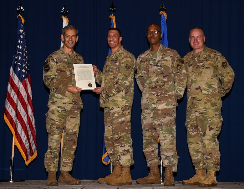 Service members receive an award and pose for a photo.