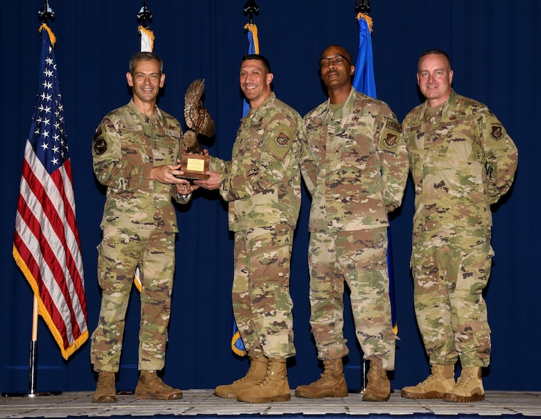 Service members receives a trophy and poses for a photo.