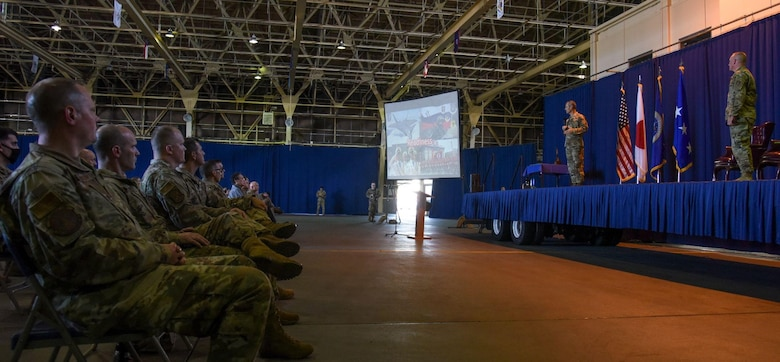 Service members listening to another service member  speaking on a stage.