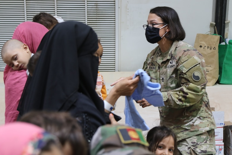 A U.S. Army National Guard Soldier with Task Force Spartan, U.S. Army Central, assists families evacuated from Afghanistan as they arrive at Camp Buehring, Kuwait, Aug. 23, 2021. U.S. Army Soldiers continue to work with the U.S. Central Command and the State Department to support Afghanistan evacuation efforts with transportation, security, logistics and medical assistance at locations in Kuwait.