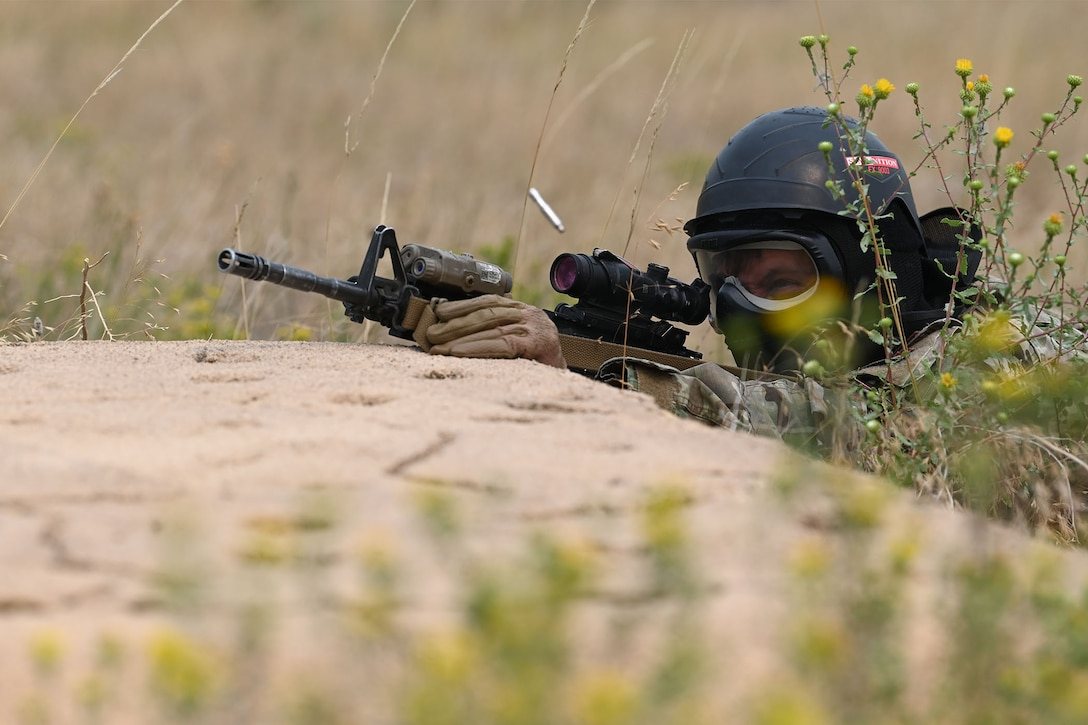 A defender from the 841st Missile Security Forces Squadron plays the role of an enemy combatant and fires simulated rounds with his M4 carbine during a training exercise Aug. 17, 2021, at the firing range on Fort Harrison, Mont. Simulated enemy combatants hid behind rocks, within tall grass and inside of buildings to test defenders' lethality and teamwork in high-pressure situations. (U.S. Air Force photo by Airman Elijah Van Zandt)
