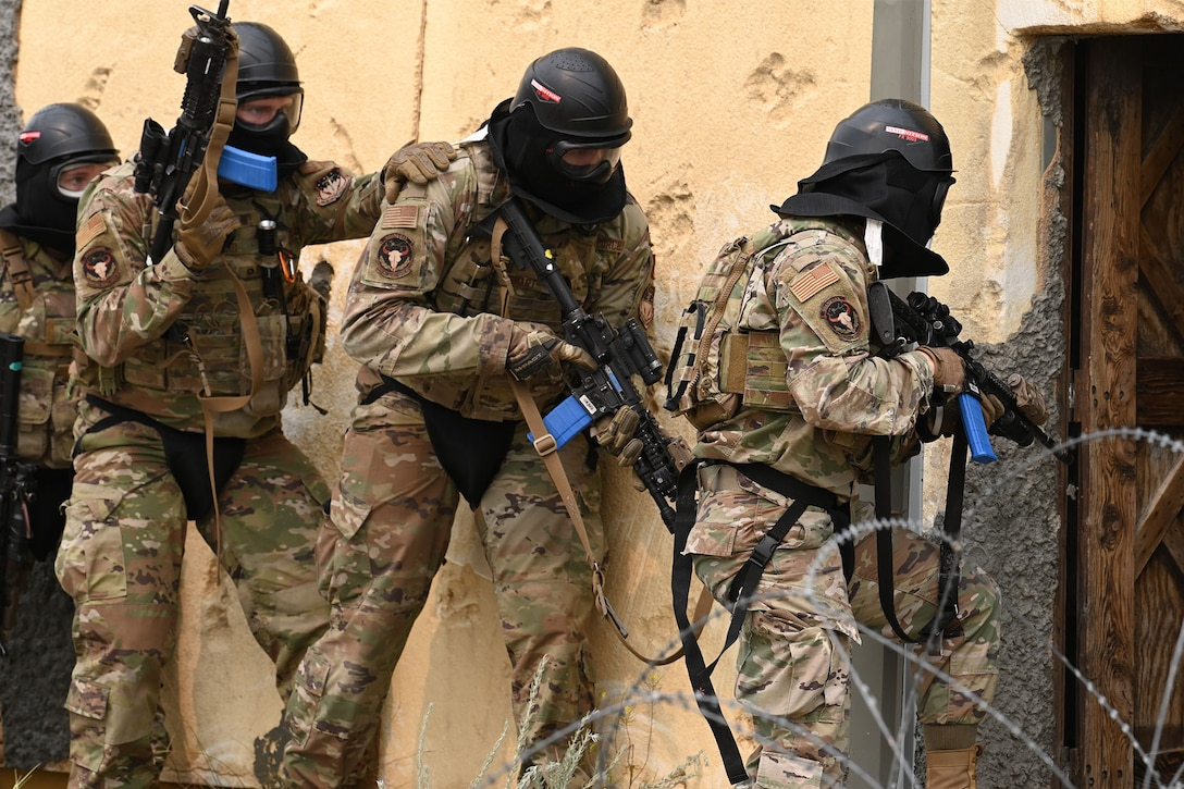 Defenders from the 841st Missile Security Forces Squadron prepare to breach a building during a training exercise Aug. 17, 2021, at the firing range village on Fort Harrison, Mont. Defenders use verbal and nonverbal commands to execute group movements while staying alert with weapons drawn to defend themselves against enemy combatants. (U.S. Air Force photo by Airman Elijah Van Zandt)
