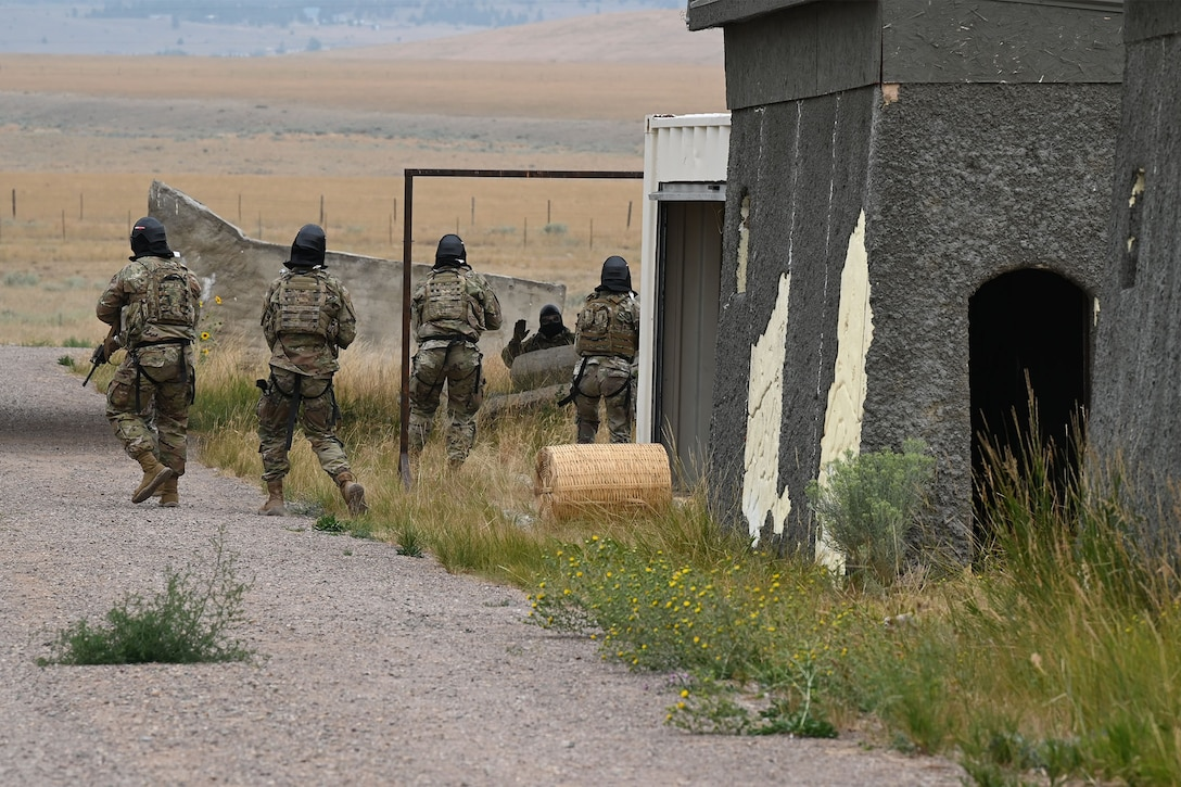 Defenders from the 841st Missile Security Forces Squadron navigate through a mock village during a training exercise Aug. 17, 2021, at the firing range on Fort Harrison, Mont. The exercise concluded with the simulated enemy combatants' surrender, resulting from the unity and precision. (U.S. Air Force photo by Airman Elijah Van Zandt)