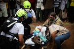 A service member and several civilians tend to a person in a stretcher on the ground.