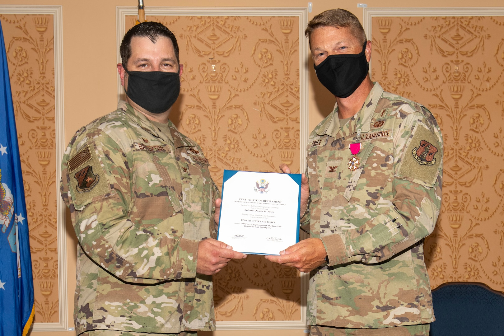 Col. Christopher G. Batterton, 192nd Wing commander, left, and Col. Jason R. Price, outgoing 192nd Medical Group commander, pose for a photo holding Price's certificate of retirement.