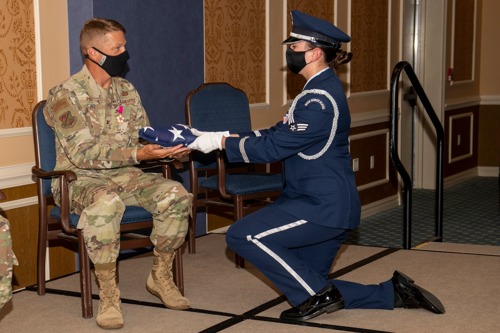 A member of the Honor Guard kneels before Col. Jason Price, outgoing 192nd Medical Group commander, and presents a folded U.S. flag to him upon his retirement.