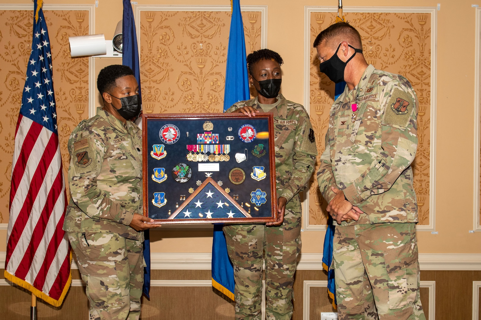 Two members of the 192nd Medical Group hold a shadow box as Col. Jason Price, outgoing MDG commander, looks at it.