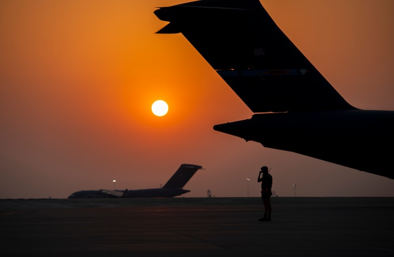 A member from the 379th Air Expeditionary Wing prepares to marshal a C-17 Globemaster lll Aug. 23, 2021, at Al Udeid Air Base, Qatar.