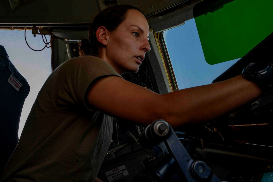 Female pilot conducts pre-flight checks in cockpit of aircraft