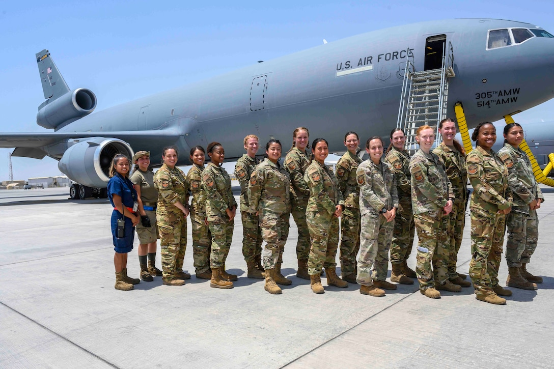 A group of female Airmen pose in front of a KC-10 Extender aircraft
