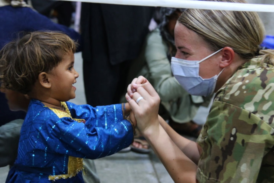 A soldier clasps a child's hands as they look at each other and smile.
