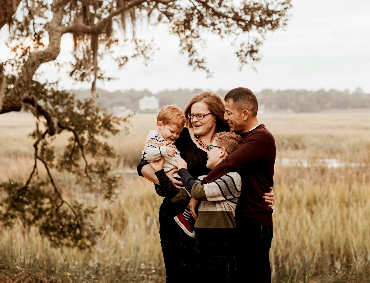 A family poses for a photo in a grassy field.