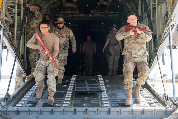 Airmen with rifles exiting aircraft.