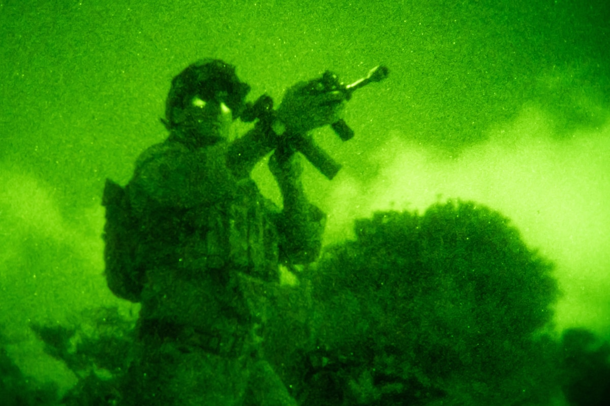 A service member stands and  holds his weapon in a green image.