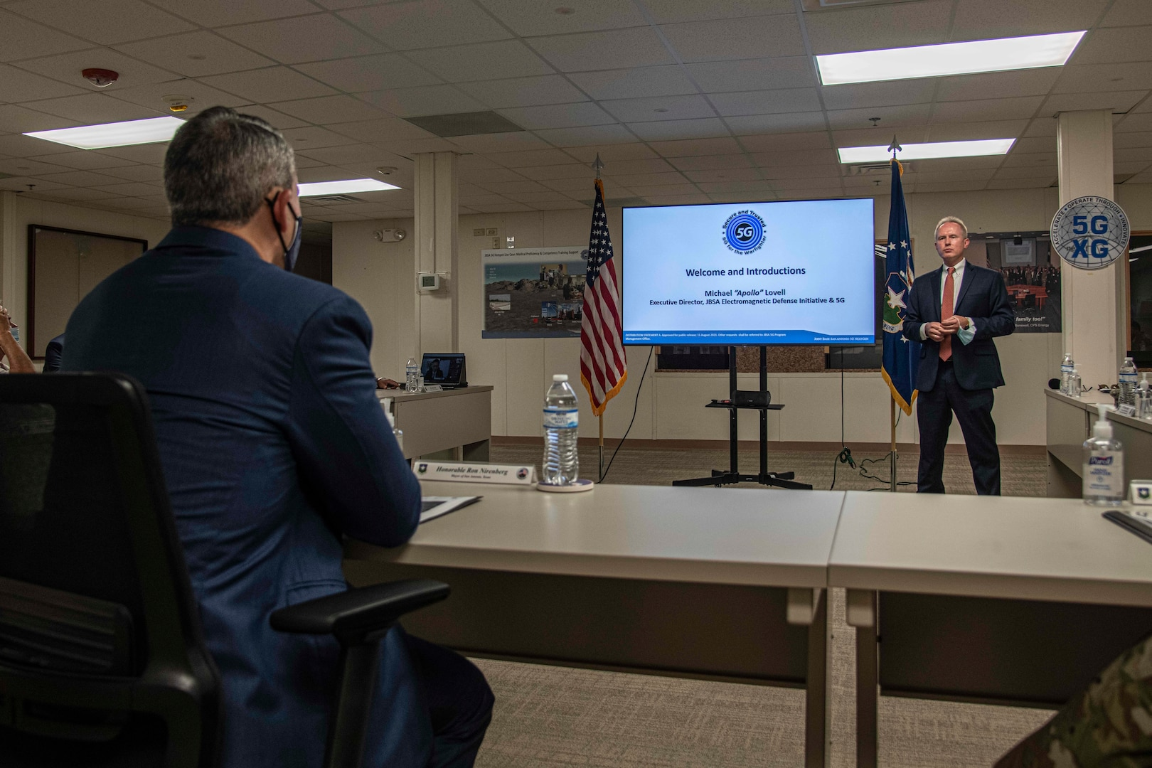 Man briefing in front of a video presentation