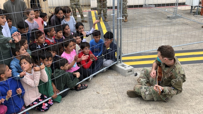 A U.S. Air Force Airman plays the ukulele for children from Afghanistan during Operation Allies Refuge at Ramstein Air Base, Germany, Aug. 24, 2021. Ramstein AB is providing safe, temporary lodging for evacuees. Many service members are also volunteering to raise morale for evacuees as they await transportation to more permanent resettlement locations.