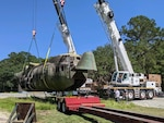 A C-130 fuselage is being placed onto a flatbed truck for transport.