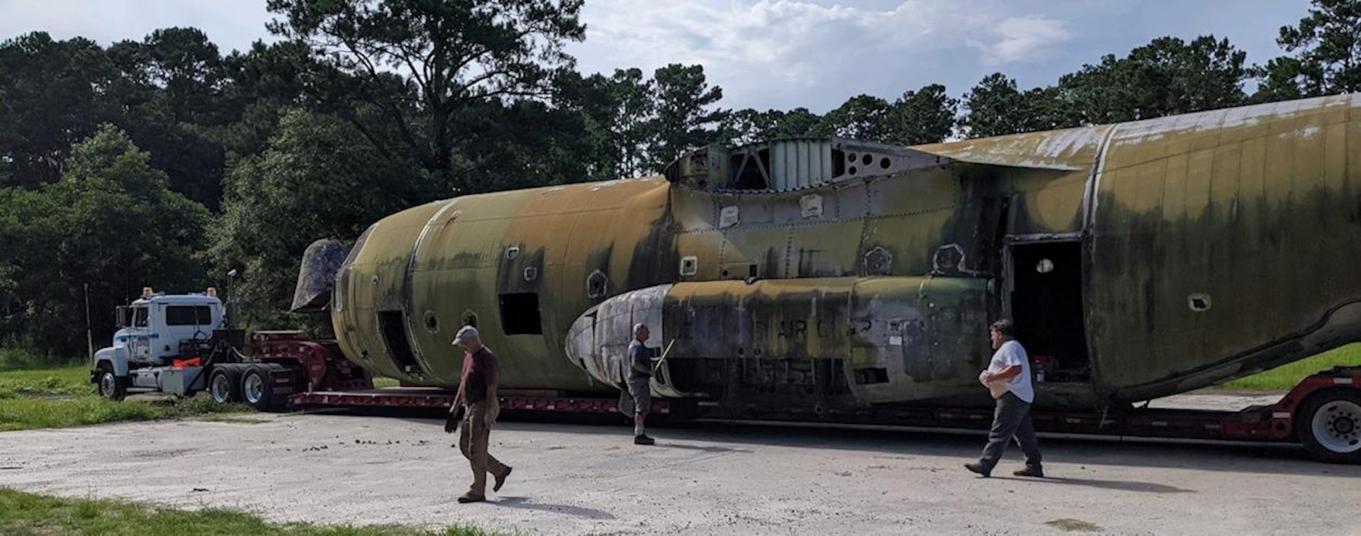 Individuals walk next to fuselage of a disable C-130