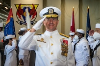 Rear Adm. Ryan Scholl, commander, Carrier Strike Group (CSG) 8 renders honors while passing through sideboys during a change of command ceremony for CSG-8 in the hangar bay of the Nimitz-class aircraft carrier USS Harry S. Truman (CVN 75).