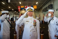 Vice Adm. Daniel Dwyer, commander, U.S. Second Fleet, renders honors while passing through sideboys during a change of command ceremony for Commander, Carrier Strike Group (CSG) 8 in the hangar bay of the Nimitz-class aircraft carrier USS Harry S. Truman (CVN 75).