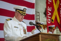 Cmdr. Chris Hester delivers an invocation during a change of command ceremony for Commander, Carrier Strike Group (CSG) 8 in the hangar bay of the Nimitz-class aircraft carrier USS Harry S. Truman (CVN 75).