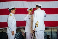 Rear Adm. Curt Renshaw, commander, Carrier Strike Group (CSG) 8, right, receives a salute from Vice Adm. Daniel Dwyer, commander, U.S. Second Fleet, middle, after relieving Rear Adm. Ryan Scholl, left, during a change of command ceremony for CSG-8 in the hangar bay of the Nimitz-class aircraft carrier USS Harry S. Truman (CVN 75).