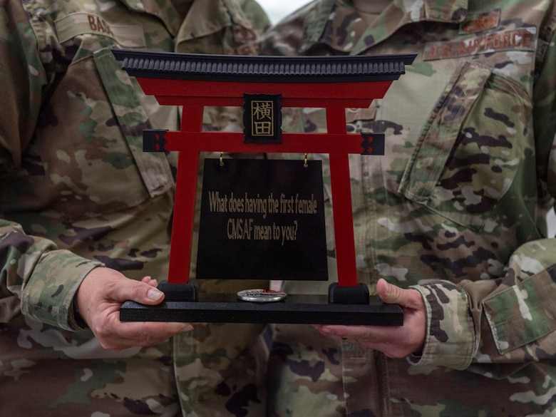 Airmen from the 374th Airlift Wing present a parting gift to Chief Master Sergeant of the Air Force JoAnne S. Bass at Yokota Air Base, Japan, Aug. 26, 2021. Bass embodies the highest enlisted level of leadership and provides direction by representing Airmen's interests to the American public and the U.S. government. (U.S. Air Force photo by Senior Airman Brieana E. Bolfing)