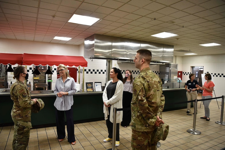 Two ladies listen to a military member in the Base's dining facility.
