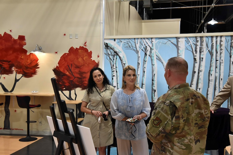 Two ladies listen to a military member in front of a board with renovation plans.