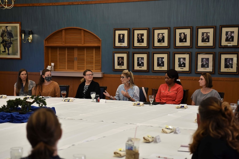 A group of ladies talk around a big table.