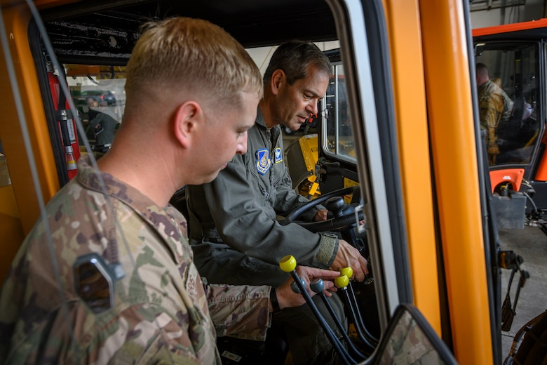 A military member in a heavy operating vehicle is being instructed by another military member.