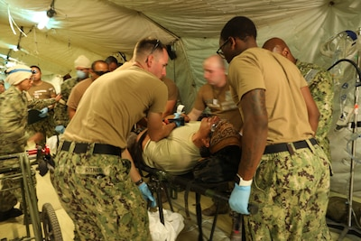 CAMP PENDLETON, Calif. (June 21, 2021) - Medical personnel assigned to Navy Expeditionary Medical Facility - M care for a simulated patient during a training exercise at Naval Expeditionary Medical Training Institute at Camp Pendleton, California.  The evolution evaluated the EMF's patient processing and coordination across functional areas.  As a result, the EMF was certified with Tier 1 capability, with the ability to deploy and provide combat operations medical support to U.S. Fleet Forces.  (U.S. Navy photo by Hospital Corpsman 1st Class Nesinee Weber, Naval Expeditionary Medical Training Institute/ Released).