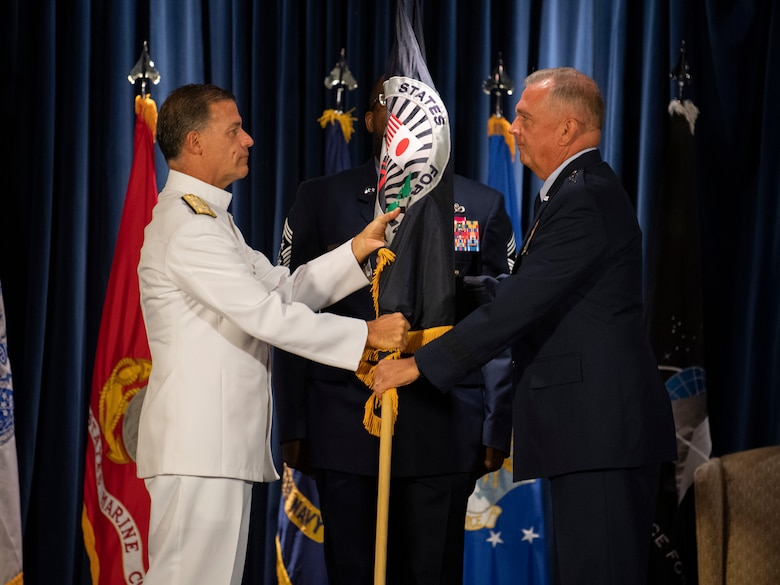 U.S. Admiral John C. Aquilino, U.S. Indo-Pacific Command commander, passes the U.S. Forces Japan guidon to Lt. Gen. Ricky N. Rupp, USFJ and 5th Air Force incoming commander, during a change of command ceremony at Yokota Air Base, Japan, Aug. 27, 2021.
