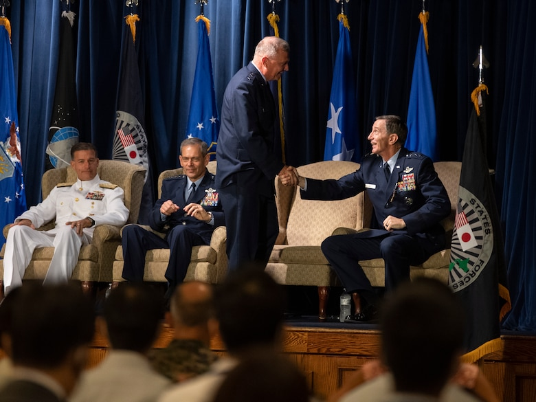 Lt. Gen. Kevin B. Schneider, former U.S. Forces Japan and 5th Air Force commander, congratulates Lt. Gen. Ricky N. Rupp, USFJ and 5th AF commander, during the USFJ and 5th AF change of command ceremony at Yokota Air Base, Japan, Aug. 27, 2021. During the ceremony, Rupp assumed command of USFJ and 5th AF from Schneider. (U.S. Air Force photo by Senior Airman Brieana E. Bolfing)