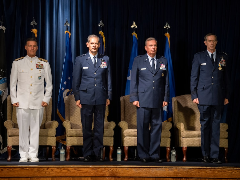 The official party stands at attention during the U.S. Forces Japan and 5th Air Force change of command ceremony at Yokota Air Base, Japan, Aug. 27, 2021. During the ceremony, Lt Gen. Ricky N. Rupp assumed command of USFJ and 5th AF from Lt. Gen. Lt. Gen. Kevin B. Schneider. (U.S. Air Force photo by Senior Airman Brieana E. Bolfing)