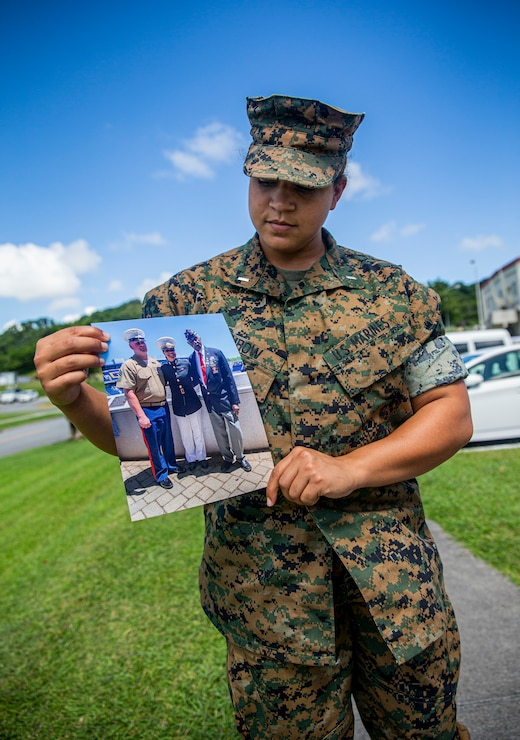 U.S. Marine Corps 1st Lt. Ashleigh Fairow, the Communication Strategy and Operations officer with Headquarters and Support Battalion, Marine Corps Installations Pacific, examines a photo of her family on Camp Foster, Okinawa, Japan, Aug. 27, 2021. A native of Jacksonville, North Carolina, Fairow became a commissioned officer in 2019 after earning a Bachelor of Science in English Studies and graduating from the U.S. Naval Academy at the age of 23. Her grandfather, retired Sgt. Ivor Griffin, enlisted in the Marine Corps in 1945, making history as he became one of the 20,000 African-Americans trained to become Marines at Montford Point Camp, Camp Lejeune, North Carolina. (U.S. Marine Corps photo by Lance Cpl. Alex Fairchild)