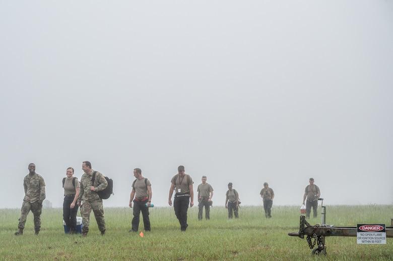 A photo of Airmen walking in a field in the mist.