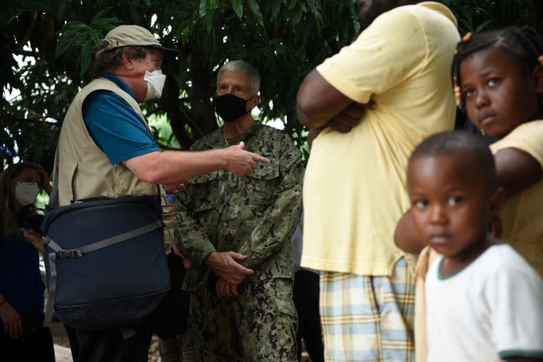 U.S. Navy Adm. Craig Faller, commander of U.S. Southern Command, and Tim Callahan, the senior regional advisor for Latin America and the Caribbean with U.S. Agency for International Development, discuss community needs and damages in Maniche, Haiti, Aug. 26, 2021.