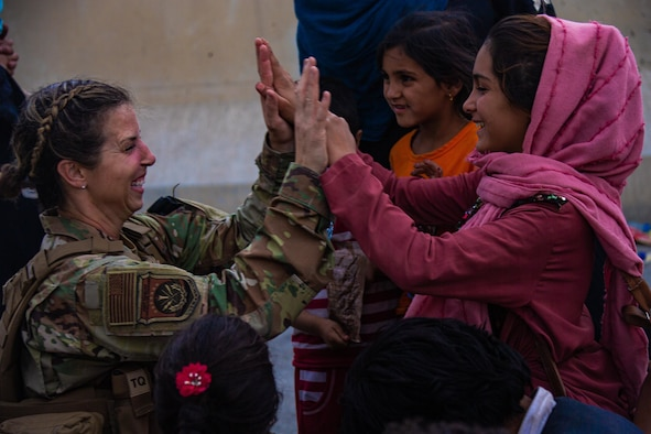 A Reserve Citizen Airmen with the Joint Task Force-Crisis Response high fives child after helping reunite their family at Hamid Karzai International Airport, Afghanistan, Aug. 20. U.S. service members are assisting the Department of State with a Non-combatant Evacuation Operation (NEO) in Afghanistan