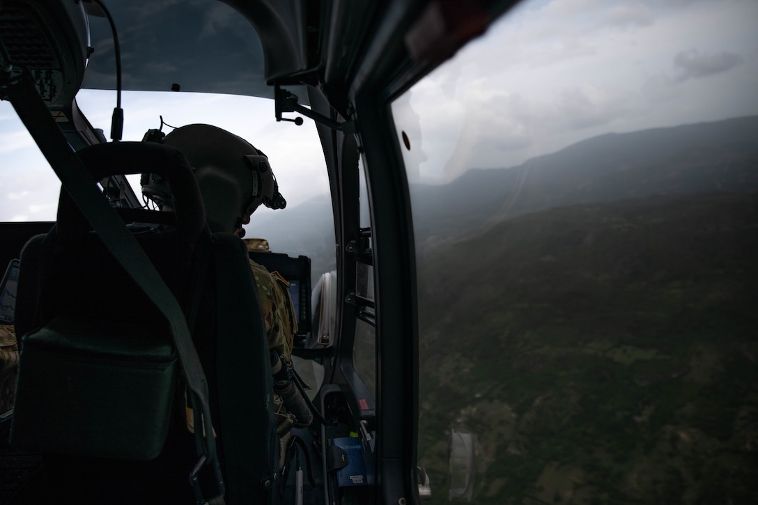 Chief Warrant Officer three (CW3) Norberto Martinez from the Puerto Rico Army National Guard Aviation looks down the right side of the aircraft during a reconnaissance flight over La Hatte, Haiti, Aug. 25, 2021.