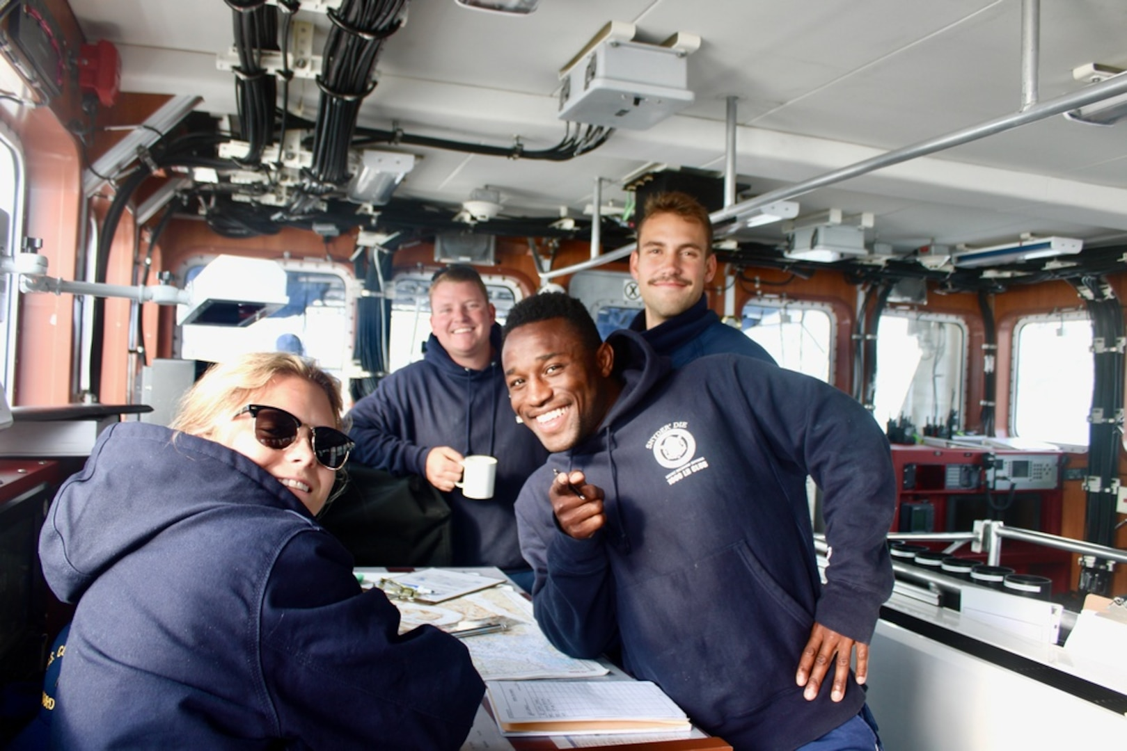 The bridge crew takes a moment for a photo on the Coast Guard Cutter Richard Snyder  in the Davis Strait on Aug. 9, 2021. Snyder worked alongside the Coast Guard Cutter Escanaba, the Royal Canadian Navy's HMCS Harry Dewolf , and HMCS Goose Bay  in Operation Nanook to enhance collective abilities to respond to safety and security issues in the High North through air and maritime presence activities, maritime domain defense, and security exercises. Left to right: Petty Officers 2nd Class Gayle Buchanan, and Zachary Weber, Seaman Kenan Carter, Ensign JT Cox. (U.S. Coast Guard photo by Coast Guard Cutter Richard Snyder)