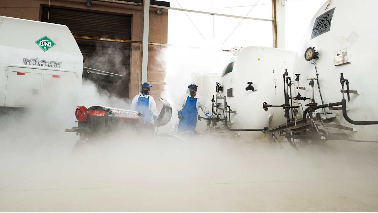 Two men in protective gear stand by as the fog from liquid nitrogen escapes from a container.