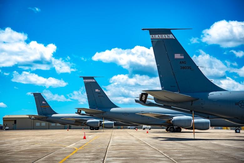 Three KC-135 sitting in a line on flight line.