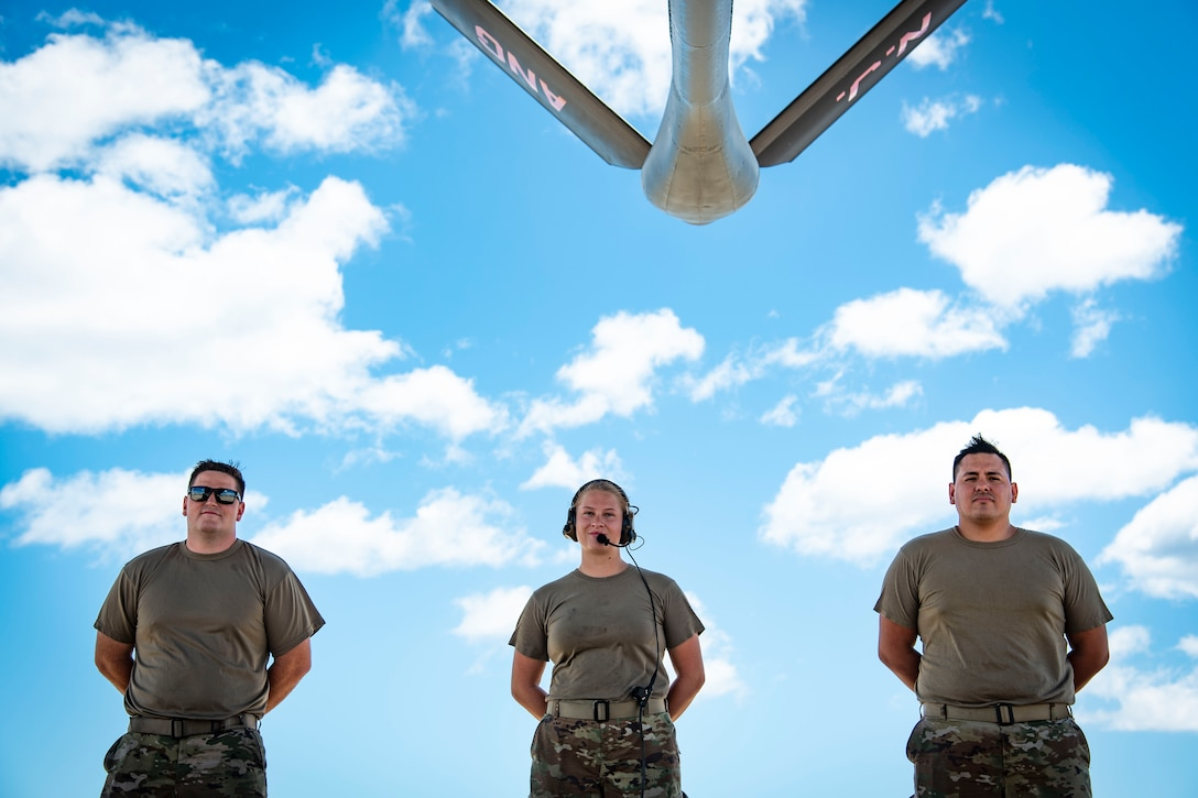 KC-135 maintainers pose outside near aircraft.