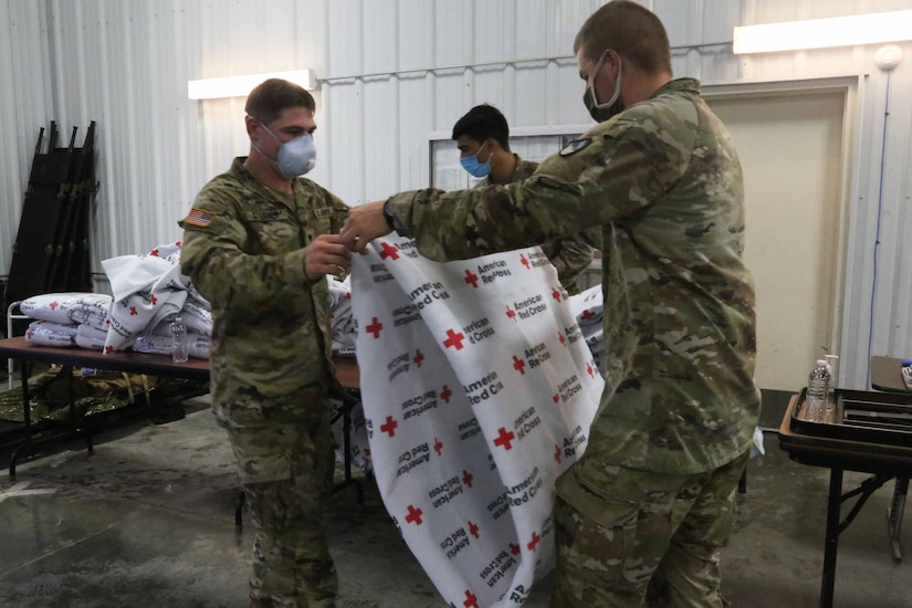 """Soldiers fold blankets that say """"Red Cross"""" on them."""